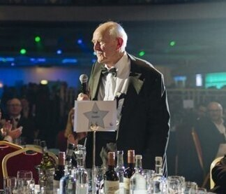 Gerry Weinbren standing with microphone at a table