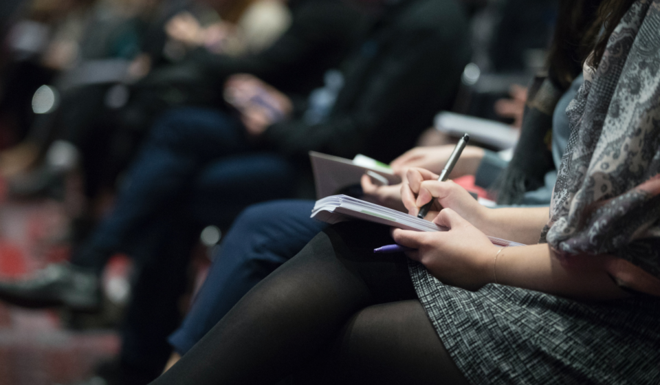 A closeup shot of a row of people sitting a conference. The women in the foreground is taking notes in a notebook.